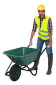 Unfriendly labourer pushing a wheelbarrow — Stock Photo