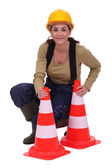 Woman kneeling by traffic cones — Stock Photo