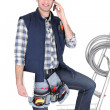 Electrician with mobile telephone stood by ladder - Stock Photo