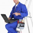 Plumber with tools and laptop — Stockfoto