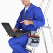 Plumber with tools and laptop — 图库照片