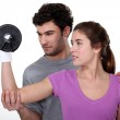 Coach helping a client lift a dumbbell — Stock Photo #17474139