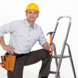 Handyman posing with his tools and a stepladder — Stock Photo #17620465