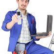 Plumber with computer showing phone — Stock Photo #17624119