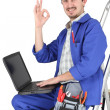 Plumber with laptop and tools on white background — Stock Photo