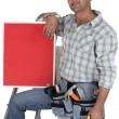 Carpenter with a red sign propped up on his knee — Stock Photo