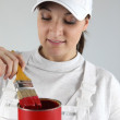 Female painter with red tin of paint and brush — Stock Photo #17624563
