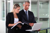 Businessman and young assistant rushing to prepare presentation — Stock Photo