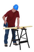 Carpenter sawing plank of wood with band-saw — Stock Photo