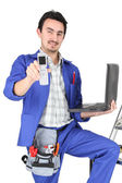 Plumber with computer showing phone — Stockfoto