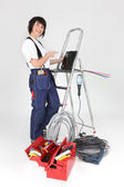 Female electrician pointing to laptop — Stock Photo