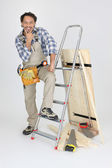 Portrait of cabinetmaker posing near ladder — Stock Photo