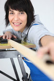 Female carpenter taking measurements — Stock Photo