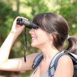 Stock Photo: Young female hiker looking through binoculars