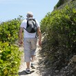 Senior man hiking by the coast — Stock Photo