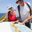 Stock Photo: Hikers looking at a map by the coast