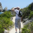 Stock Photo: Senior man using binoculars by the coast
