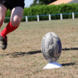 Stock Photo: Rugby player kicking ball off plastic tee