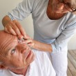 Wife helping husband with contact lenses — Stock Photo