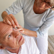 Stock Photo: Wife helping husband with contact lenses