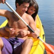 Teenage girl hanging onto her boyfriend while kayaking — 图库照片