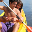 Teenage girl hanging onto her boyfriend while kayaking — Stockfoto