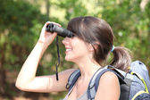 Young female hiker looking through binoculars — Stock Photo