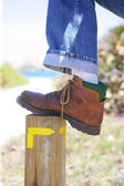 Man resting foot on wooden pole — Stock Photo