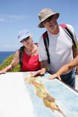 Hikers looking at a map by the coast — Stock Photo