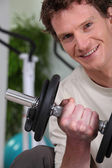 Young man using weights in a gym — Stock Photo