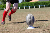 Rugby player kicking ball off plastic tee — Stock Photo