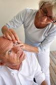 жена помогает муж с контактными линзами — Стоковое фото