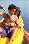 Teenage girl hanging onto her boyfriend while kayaking — Stock Photo