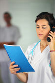 Nurse on the phone with a chart — Stock Photo