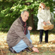 Senior couple gathering mushrooms - Stock Photo