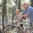 Two seniors riding bikes in the park — Stock Photo