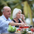 Senior friends having a meal in the garden — Stock Photo
