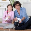 Mother and daughter playing video games — Stock Photo #18415271