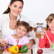 Stock Photo: Children preparing meal with mum