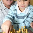 Senior man and grandson playing chess — Stock Photo #18416475