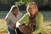 Two mature women picking chestnuts — Stock Photo
