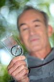 Retiree rambling through nature with compass — Stock Photo