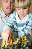 Senior man and grandson playing chess — Stock Photo