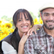 Smiling man and woman in a field of sunflowers — Stock Photo #18421569
