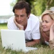 Couple lying in the grass looking at a laptop — Stock Photo