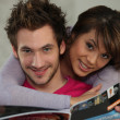Stock Photo: Couple reading magazine