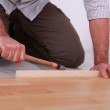 Man hammering laminate flooring into place — Stock Photo