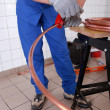 Plumber cutting copper pipe - Stock Photo