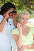 Young couple with binoculars — Foto Stock
