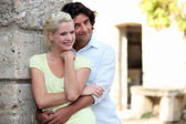 Couple leaning against stone wall — Stock Photo